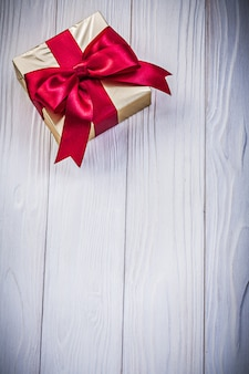 Gift box in glittery paper with bow on wooden board holidays concept