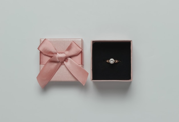 Gift box and gold ring with diamond on a pink pastel background. wedding concept. jewelry. top view. flat lay