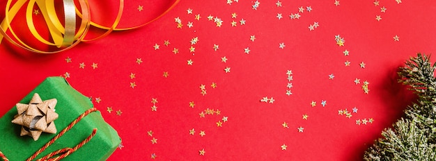 Gift box, golden toys on red background