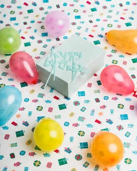 Gift box and happy birthday sign between bright balloons