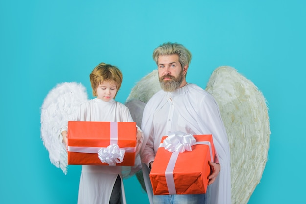 Gift box happy father in angel costume with little son angel holds present cute angel valentines day