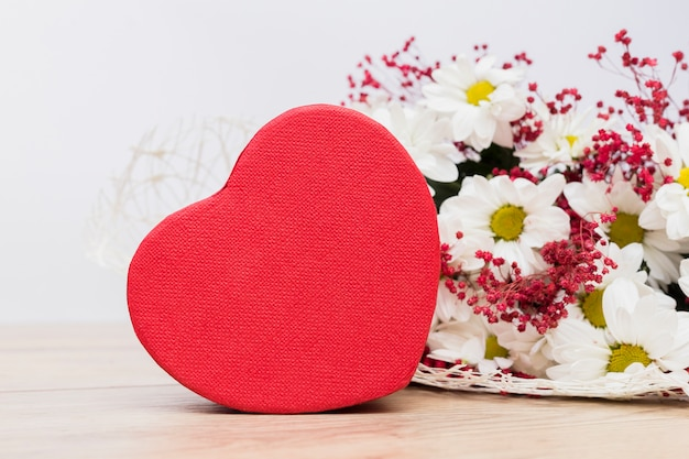Gift box in heart shape with flowers bouquet on table