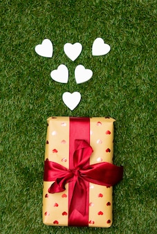 Gift box and heart shapes on green grass.