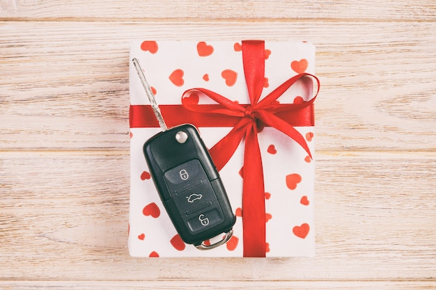 Gift box in heart wrapping paper and car key