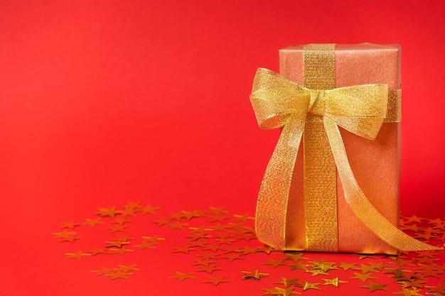텍스트를 위한 공간이 있는 별빛 배경에 금색 활이 있는 금색 포장지에 있는 선물 상자