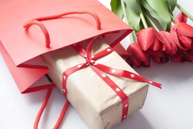 ショッピングバッグのギフトボックスとテーブルの上の赤いチューリップの花