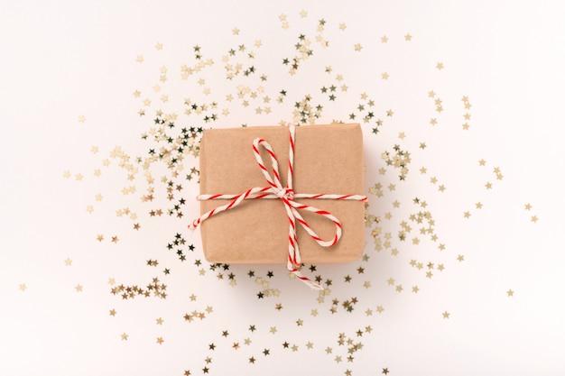 Подарочная коробка из крафт-бумаги с бело-красной новогодней лентой и золотыми конфетными звездами на бежевом фоне