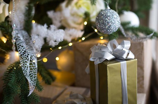 Подарочная коробка в золотой упаковке и серебряном банте под елку с белым декором. новый год, канун рождества, поздравления семье, уюта и ожидание чуда
