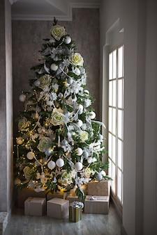 白い装飾が施されたクリスマスツリーの下に金のパッケージと銀の弓のギフトボックス