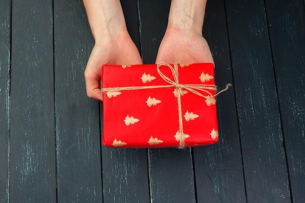 나무 테이블에 여자 손에 선물 상자