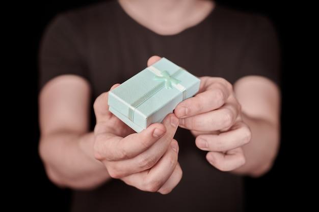 Подарочная коробка в руке. валентина подарок. маленькая юбилейная подарочная коробка от мужчины. маленькая концепция-сюрприз. черный фон.