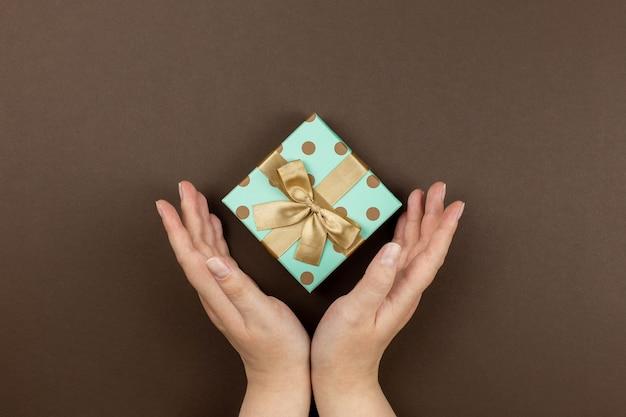 お祝いのイベント、母親、バレンタイン、記念日、クリスマス、暗い背景の誕生日のための手にギフトボックス。