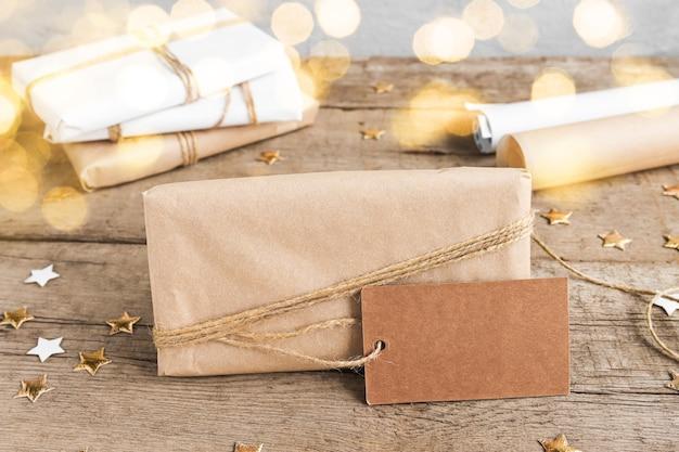 Подарочная коробка из крафт-бумаги крупным планом с биркой для расфокусированных огней, вид спереди