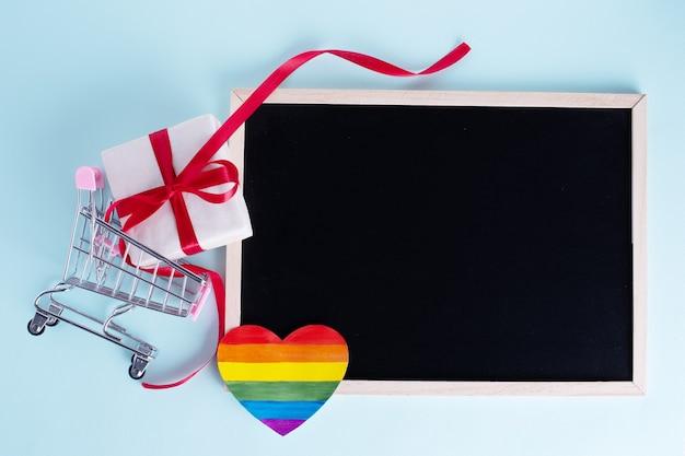Подарочная коробка в тележках, радужное бумажное сердце и пустая доска с копией пространства на голубом фоне
