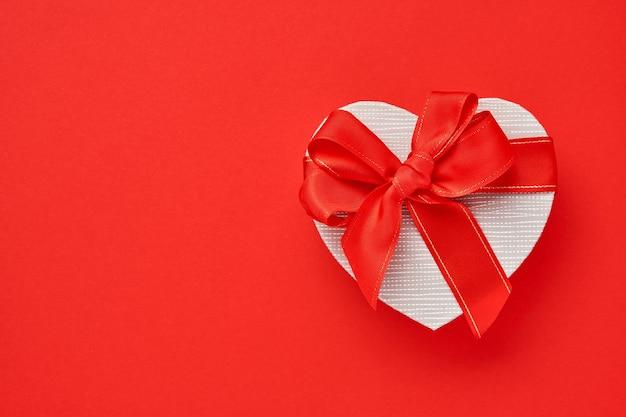Подарочная коробка в форме сердца с красной лентой на красном фоне. открытка концепции дня святого валентина.