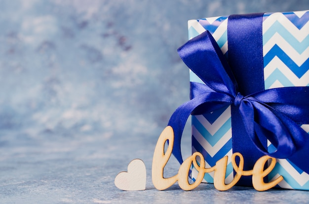 Gift box and the inscription love on blue background. gifts concept for men.