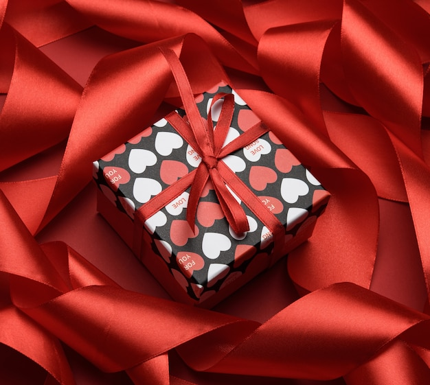 Gift box is packed in red paper and curled silk ribbon on red, valentine's day