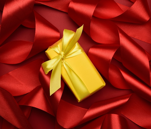 Gift box is packed in yellow paper and curled red silk ribbon on red