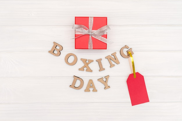 Above gift box is tied with a ribbon with words boxing day and red tag