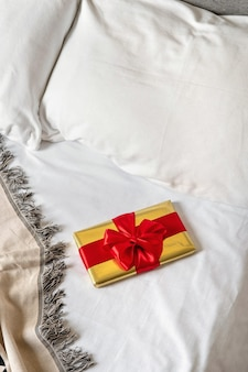A gift box lies in bed early in the morning. content for honeymooners and lovers for valentine's day.