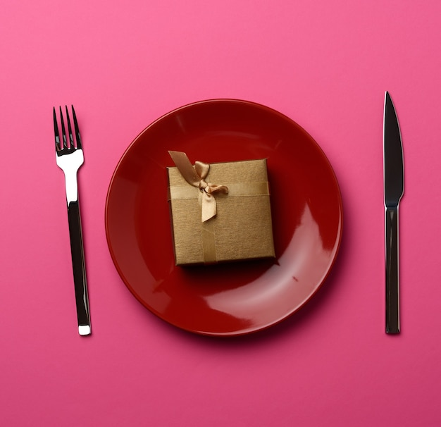 Подарочная коробка лежит в круглой керамической тарелке и вилке с ножом.