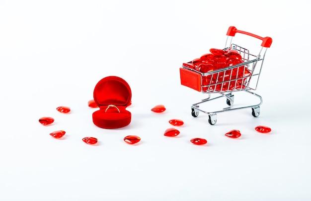 Подарочная коробка из красного бархата с кольцом и корзиной-сердечком на белой стене. день святого валентина.