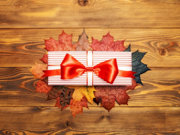 Gift box and maple leaves on the wooden board