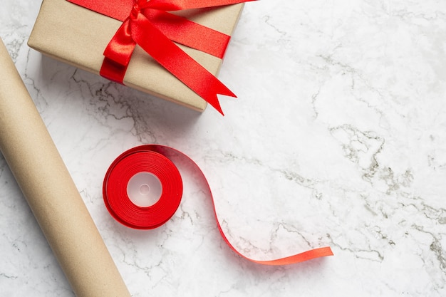 Gift box and material of gift wrapping placed on the white marble floor