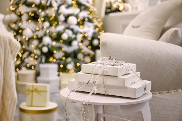 リビングルームの飾られたクリスマスツリーの近くのギフトボックス