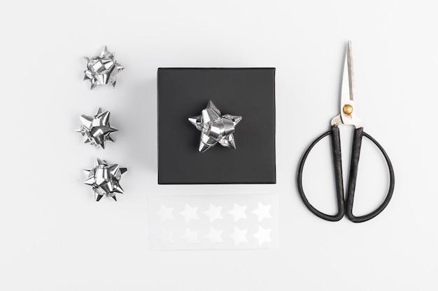 Gift box near decorative bows and scissors