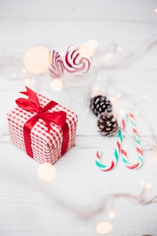 Gift box near glass with lollipops, candy canes and illuminated fairy lights
