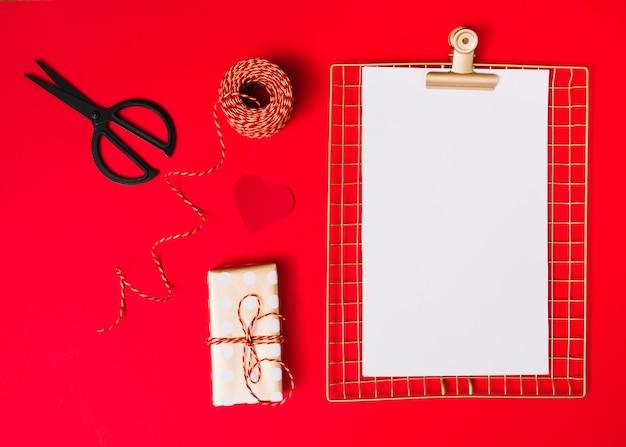Gift box near ornament heart, clipboard, scissors and threads