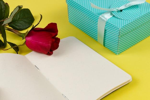 Подарочная коробка рядом с блокнотом и цветком.