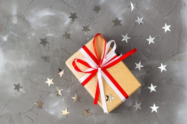 Подарочная коробка из крафт-бумаги с бантом и серебряными звездами
