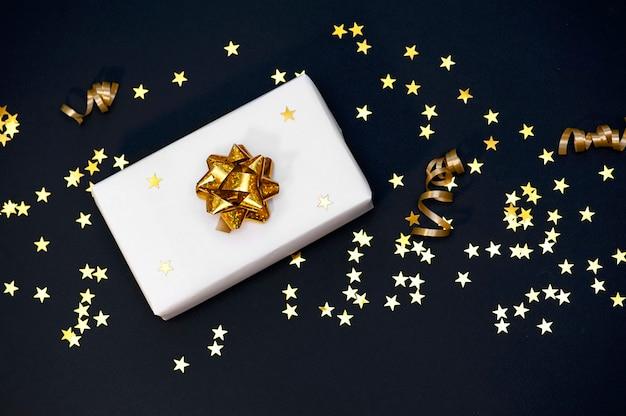 Подарочная коробка на черном фоне с золотым конфетти праздничный фон