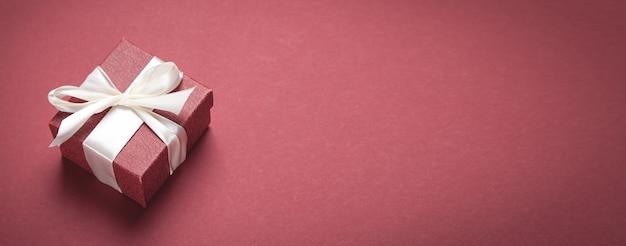 Подарочная коробка на фоне бордо.
