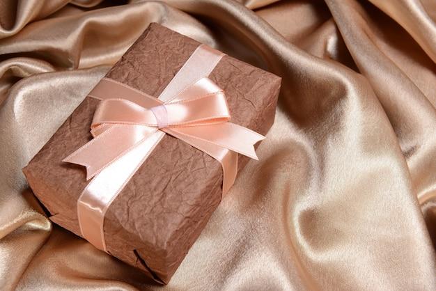 Подарочная коробка на столе на шелке, вид сверху