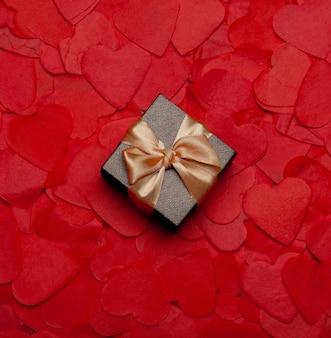 Подарочная коробка на фоне бумажных сердечек