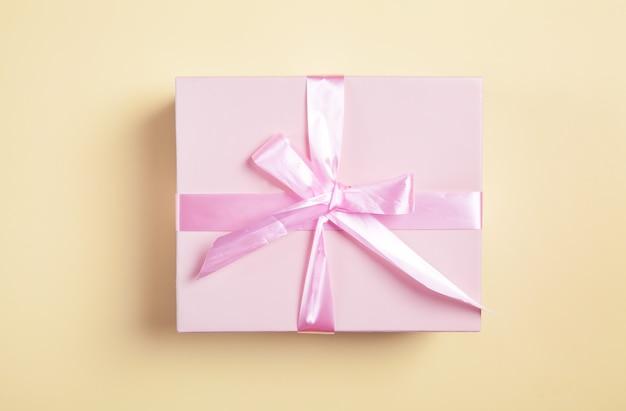 Подарочная коробка на желтой поверхности. красивый подарок