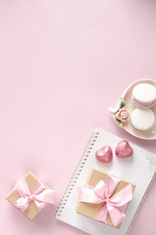 ピンクのテーブルトップビューでギフトボックスまたはギフトボックスと花。