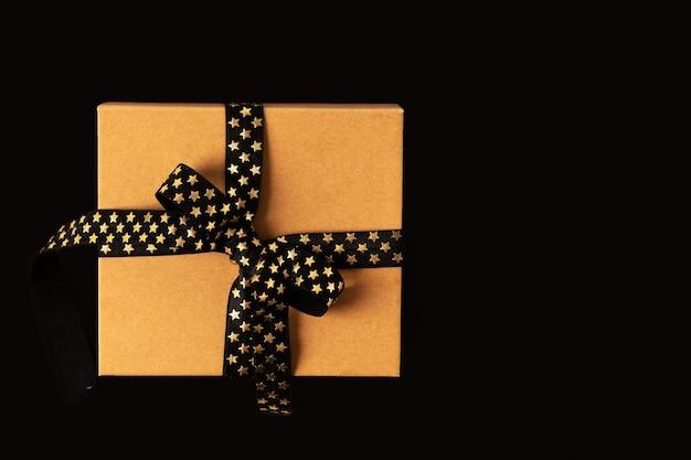 Подарочная коробка или подарочная коробка с черной золотой лентой на черном фоне