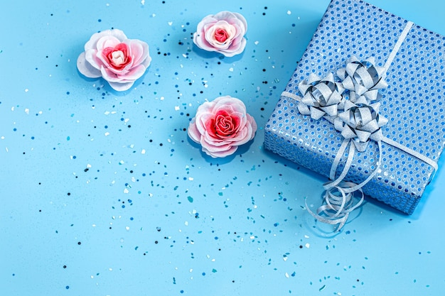 Gift box packed in blue paper on a blue background .