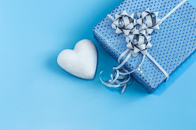 Подарочная коробка упакована в синюю бумагу на синем фоне.