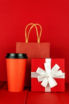 Gift box, paper craft bag and coffee cup on red room