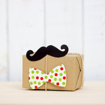 Gift box, paper mustache, tie on wooden background with copy space. happy father's day.