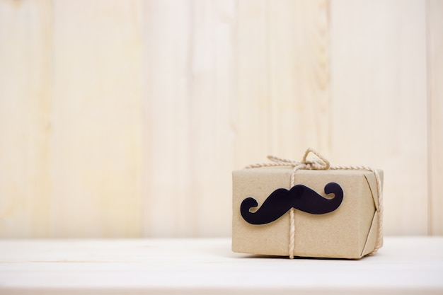 Gift box, paper mustache on wooden background with copy space. happy father's day.