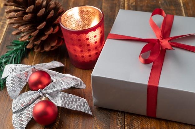 Подарочная коробка, шишка, свеча, елочный шар и бант над деревянным столом