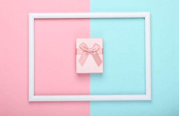 Gift box on pink blue pastel surface with white frame