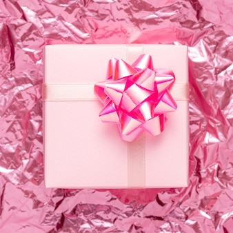 Gift box on pink crumpled foil background