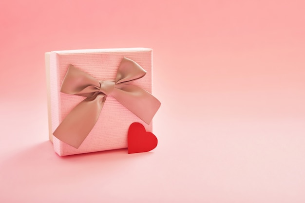 Gift box on a pink surface with hearts for valentines day